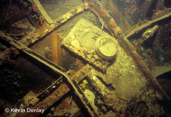 A clock dangles from a bulkhead just inside the officer's mess, or Longroom, on the wreck of Hr. Ms. De Ruyter. The wreck laid over to starboard on an angle of about 60 degrees