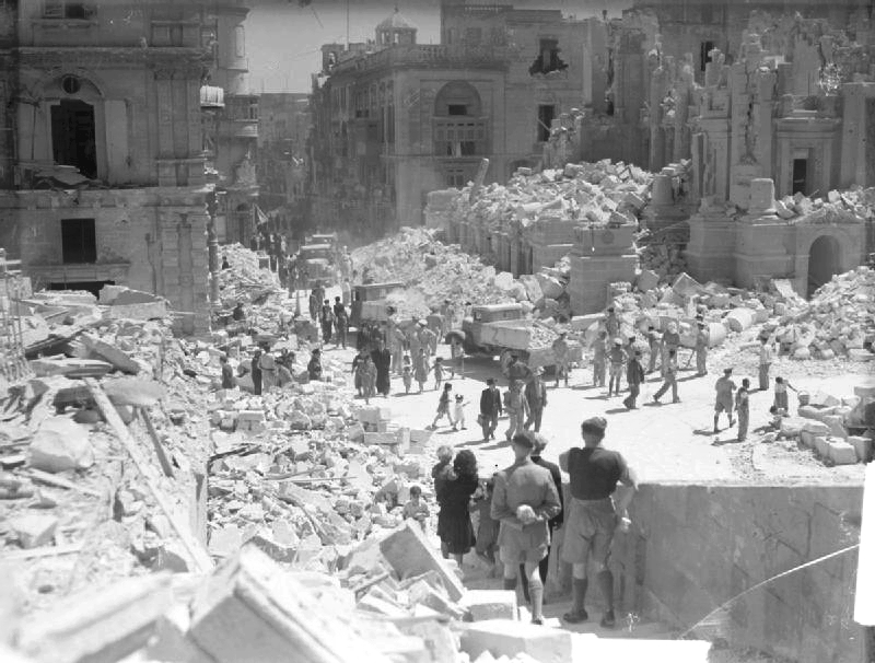 A heavily bomb-damaged street in Valletta, Malta. This street is Kingsway, the principle street in Valetta. Service personnel and civilians are present clearing up the debris. Russell, J E (Lt) - Royal Navy official photographer - This is photograph A 8701 from the collections of the Imperial War Museums (collection no. 4700-01)