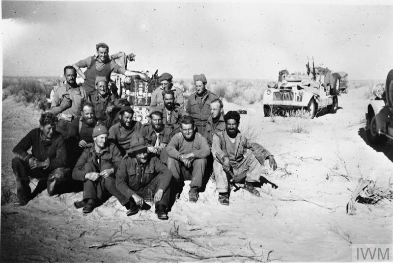 A group of Long Range Desert Group men pose for a photograph in front of their vehicles, having become the first 8th Army unit to cross the Tunisian border. At this time, LRDG patrols were being tasked by Montgomery to reconnoitre the 'going' in southern Tunisia, in case the 8th Army had to bypass the strongly held Mareth Line. Copyright: © IWM. Original Source: http://www.iwm.org.uk/collections/item/object/205125575