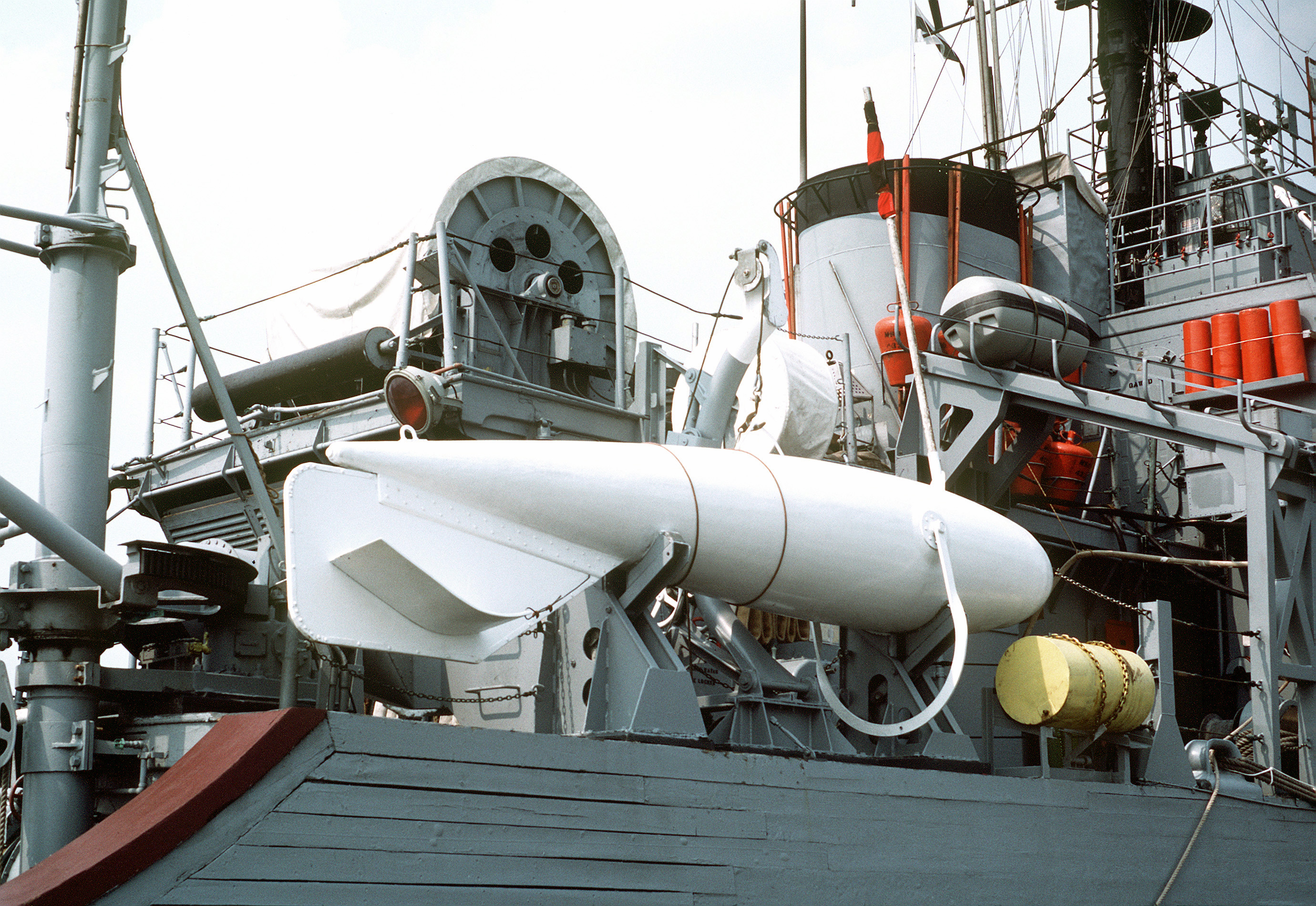 A view of the amidships section of the ocean minesweeper USS ENGAGE (MSO-433) showing a paravane in its storage rack.