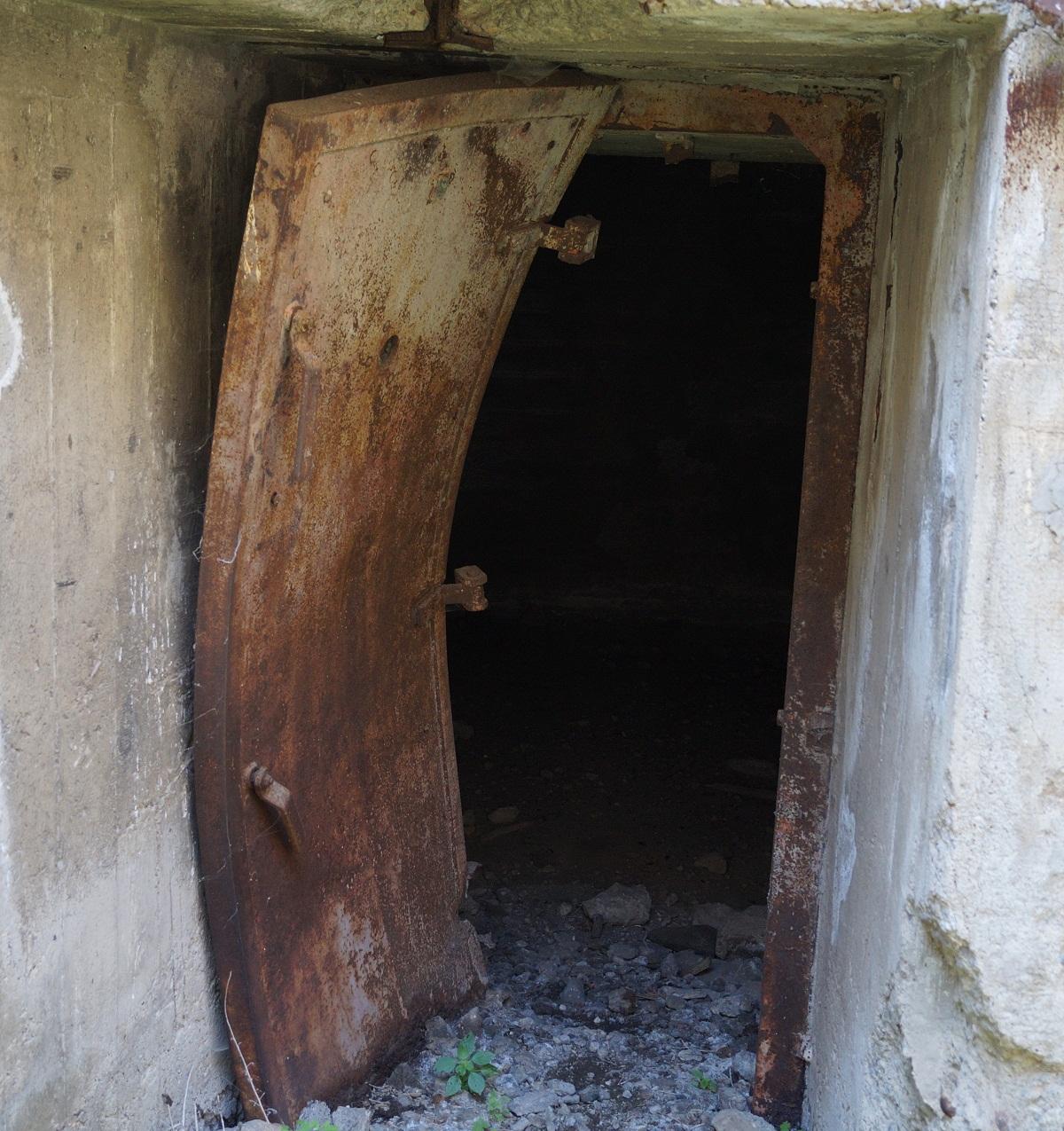 Μια βαριά θωρακισμένη πόρτα, έχει κυριολεκτικά λυγίσει, από έκρηξη στο εσωτερικό. Εντούτοις, τα πέριξ τοιχώματα είναι ανέπαφα. Δείγμα της στιβαρότητας της κατασκευής.