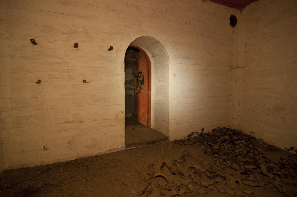 Εσωτερικός θάλαμος. Παρατηρήστε τη θωρακισμένη πόρτα, που διατηρεί την έντονη βαφή της, και τα υπολείμματα προστατευτικών καλωδίων στο πάτωμα.