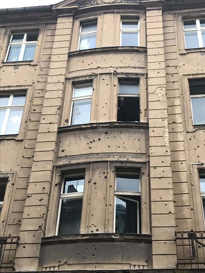 Bullet and shrapnel holes are still evident on this building, a chilling testament to the lives lost around it in 1945