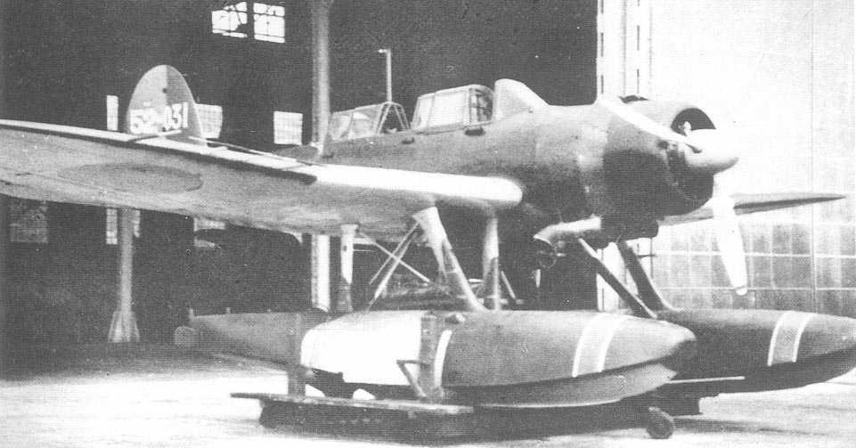 An E13A-6 outside a hangar