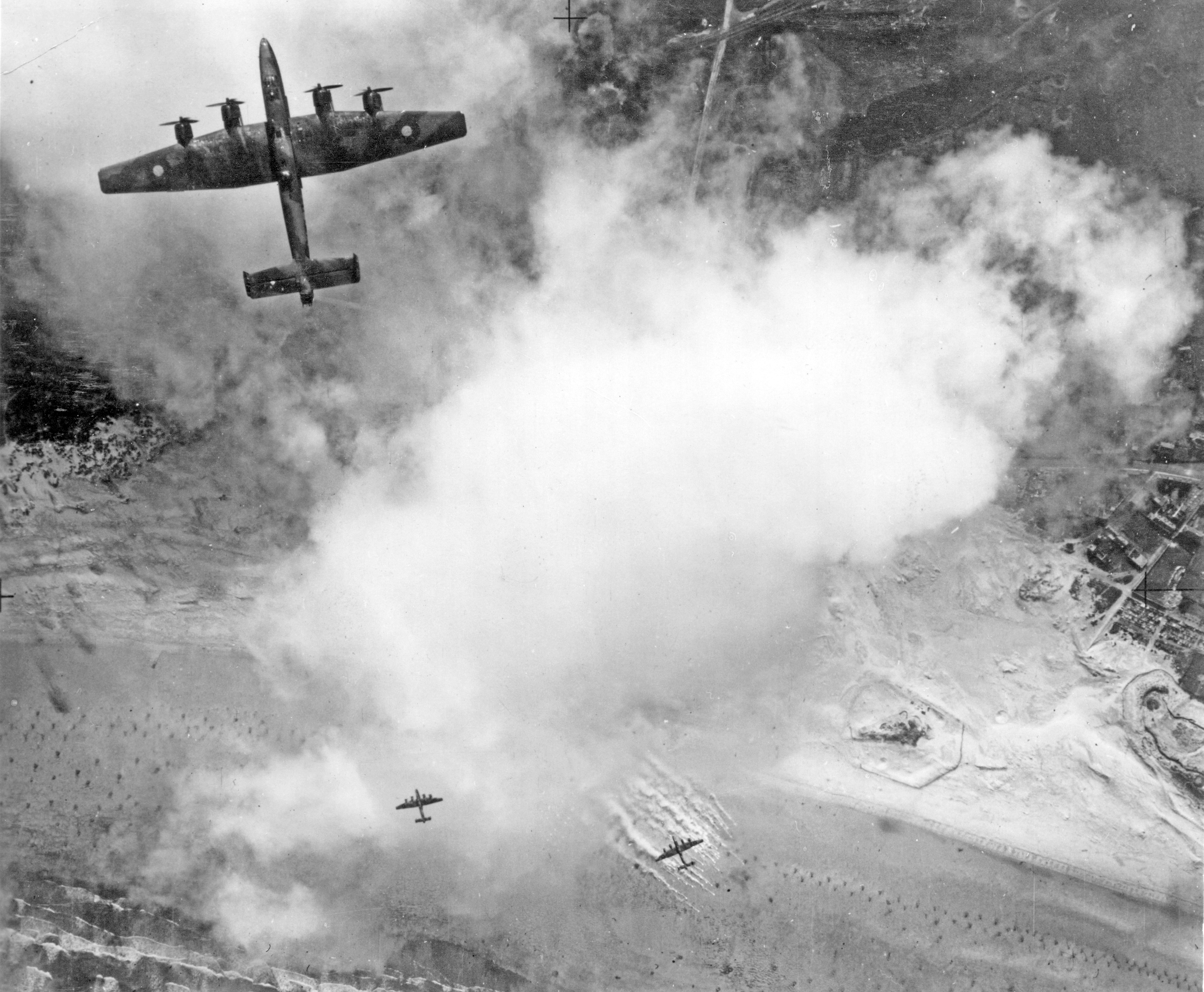 Aerial reconnaissance photograph taken during a daylight raid by 872 aircraft on German defensive positions around Calais, France, on 25 September 1944. Three Handley Page Halifaxes, photographed from an Avro Lancaster, can be seen over the target area, a coastal battery, which is obscured by low cloud. The scattered candles of a Target Indicator can be seen smoking on the beach, which is itself covered in landing obstacles.