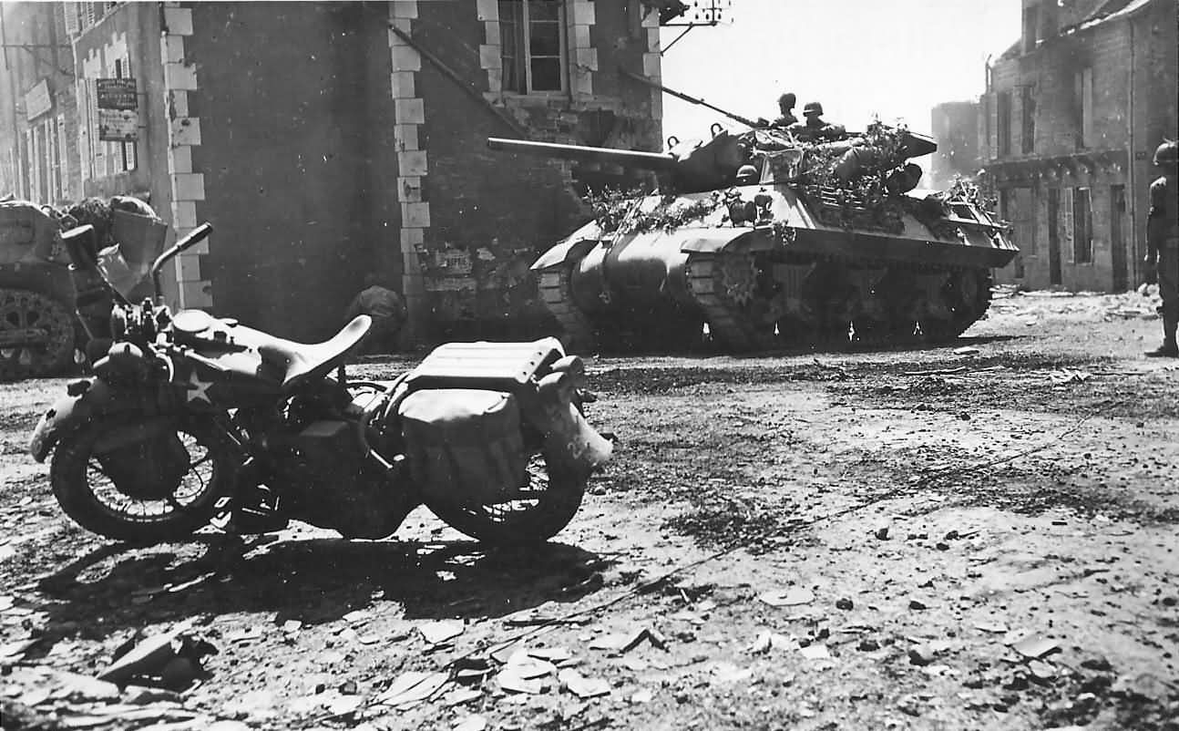 An M10 tank, with a Harley Davidson motorbike in the foreground, in the city of Percy, in August 1944
