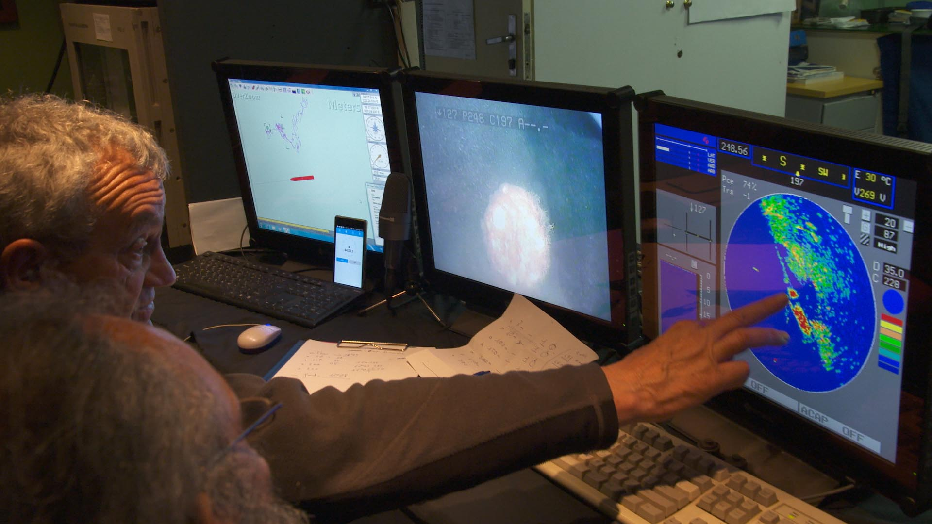 """There she is!"" The members of the exploration team check the sonar imagery of the submarine wreck on the monitors."