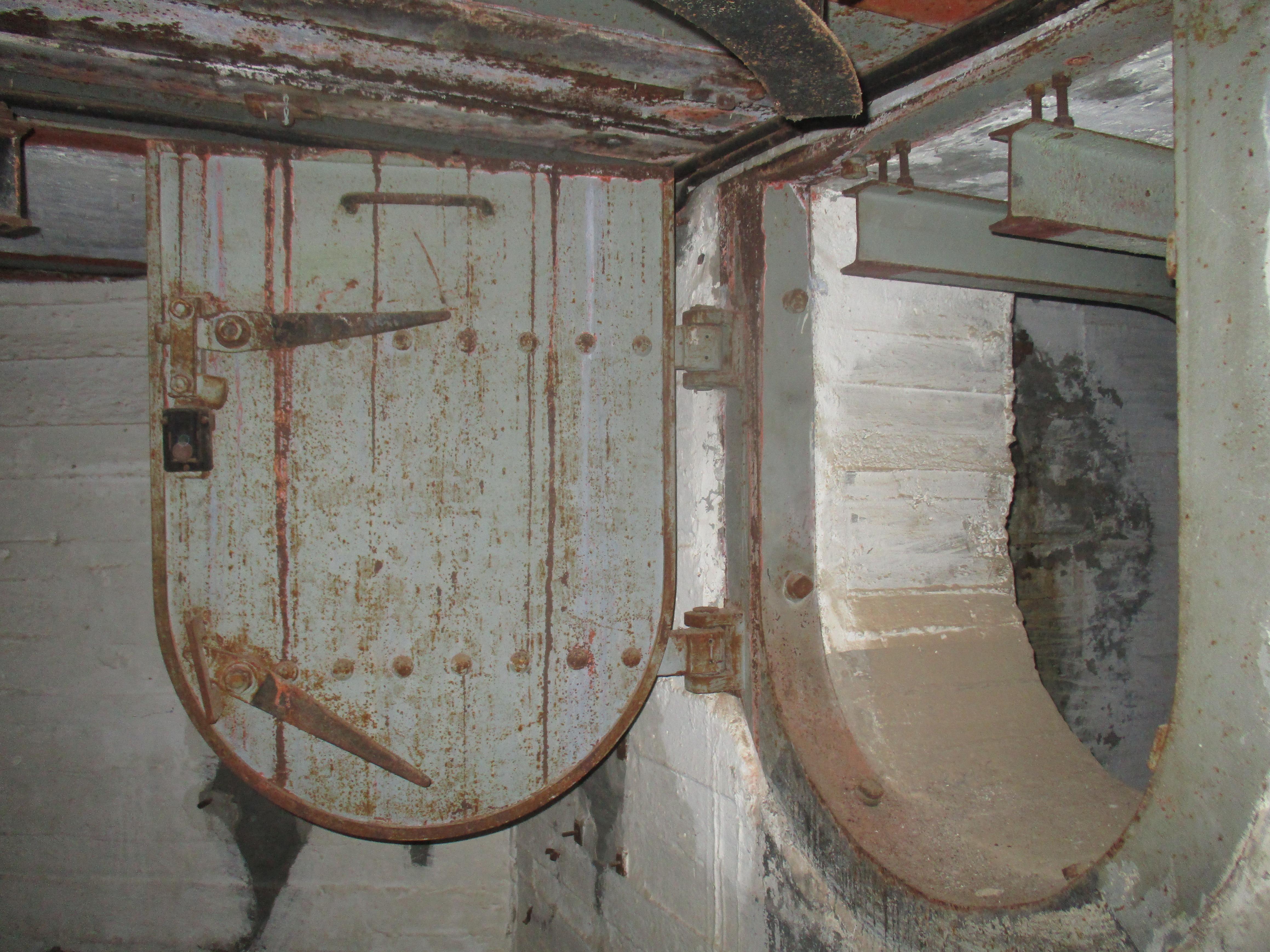 Μια αρκετά ασυνήθιστη πόρτα, σε σχήμα ασπίδας. Παρατηρήστε αριστερά την απόληξη των τροχιών μεταφοράς βλημάτων από τον διπλανό θάλαμο.