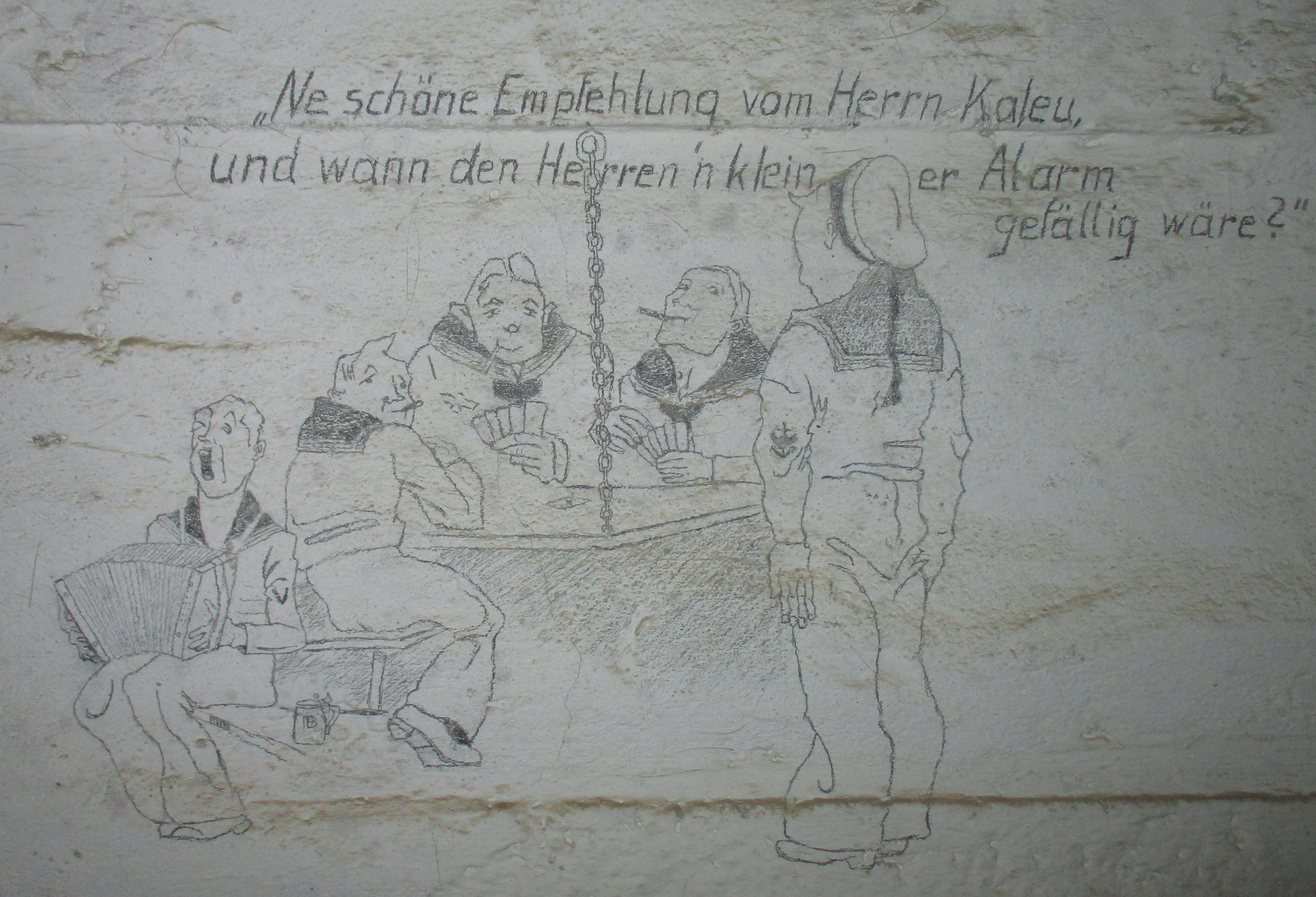 Γελοιογραφία σε τοίχο, φιλοτεχνημένη από γερμανό ναύτη, που έδρευε στο Ν.Ο.Φ. , κατά τη διάρκεια της Κατοχής. Επρόκειτο για προσωπικό της MAA-603 (Marine Artillerie Abteilung 603), δηλαδή της 603ης Ναυτικής Πυροβολαρχίας. Είναι αξιοσημείωτο ότι αυτό το μικρό «έργο τέχνης» επιβίωσε για σχεδόν 75 χρόνια, μέσα σε ένα σκοτεινό καταφύγιο.
