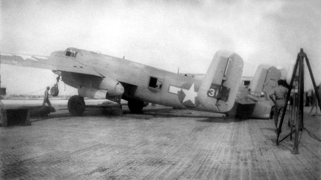 A PBJ-1H of VMB-613 on Roi Island, October 1944. The plane has been stripped of usable equipment and is awaiting disposal in the lagoon by CASU-F-20.