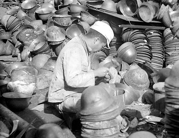 A young Japanese hired by the US Army cleans and stacks M30-32 Tetsu-bo helmets.