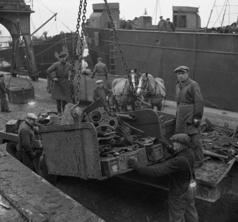 Antwerp in late 1945 early 1946, an embarkment pier for general war scrap, in this case vehicle parts and metal ammunition boxes.