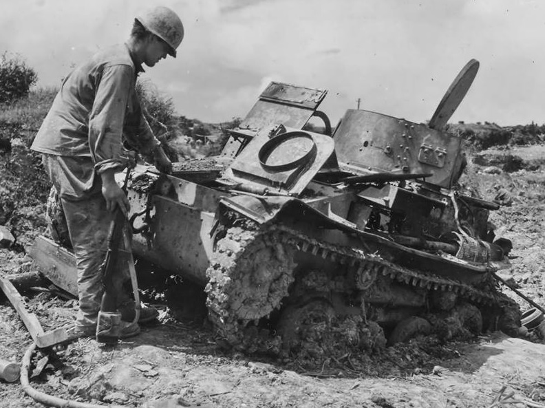 GI hooks a tow rope to a Type 97 Te-Ke tank during cleanup of the Okinawa battlefields at the end of WWII in 1945.