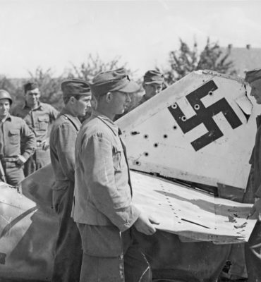German-prisoners-of-war-wearing-German-uniform-caps-dismantled-a-Messerschmitt-Me-262-jet-fighter-for-scrap-in-a-small-town-southeast-of-Wurzburg-Germany-in-the-summer-of-1945