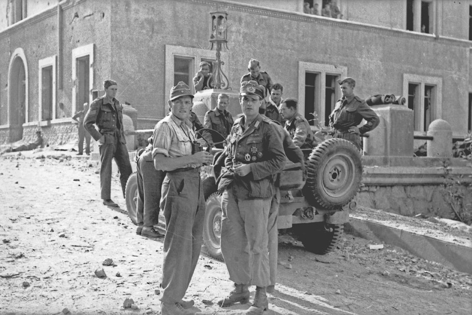 Unternehmen Leros. Hauptmann Helmut Dörr (looking directly at camera) at an assembly area for British prisoners of war, most or all of them NCOs and WOs. Bundesarchiv: BA 101I-528-2356-34