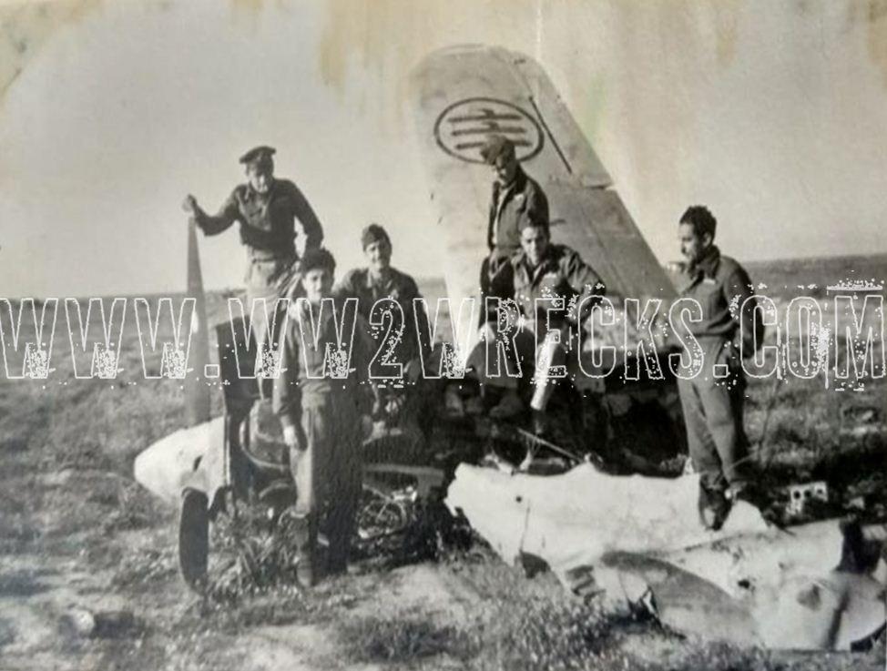 Ο Ιωάννης Κατσαρός με συναδέλφους του, σε ένα κατεστραμμένο αεροσκάφος της Regia Aeronautica, της Βασιλικής Αεροπορίας της Ιταλίας, στην έρημο της Β. Αφρικής.
