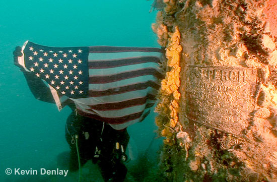 A diver holds a US flag next to the 'conning tower' of the submarine USS Perch, which we found by accident as it were while searching for HMS Exeter. Perch's name plate can clearly be seen at right