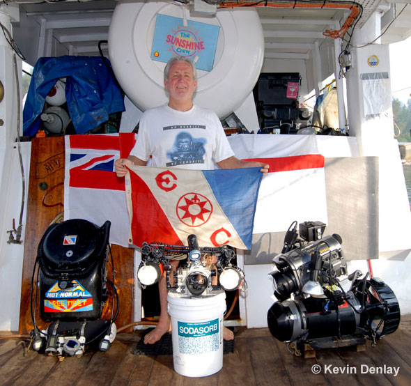 Kevin with Explorers Club Flag #46 and the 'tools of his trade' aboard MV Empress; left, his MK15.5 Closed Circuit Rebreather; centre, his housed Nikon digital camera atop a tub of Co2 absorbent for his CCR; right his Diver Propulsion Vehicle, or scooter, with a housed digital video camera mounted atop.Note Empress's on-board recompression chamber behind Kevin's head