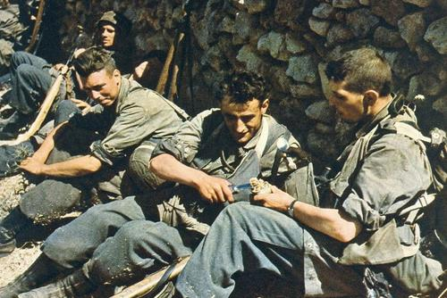 German paratroopers during a lull in the Battle of Crete. One is seen holding a gravity knife.