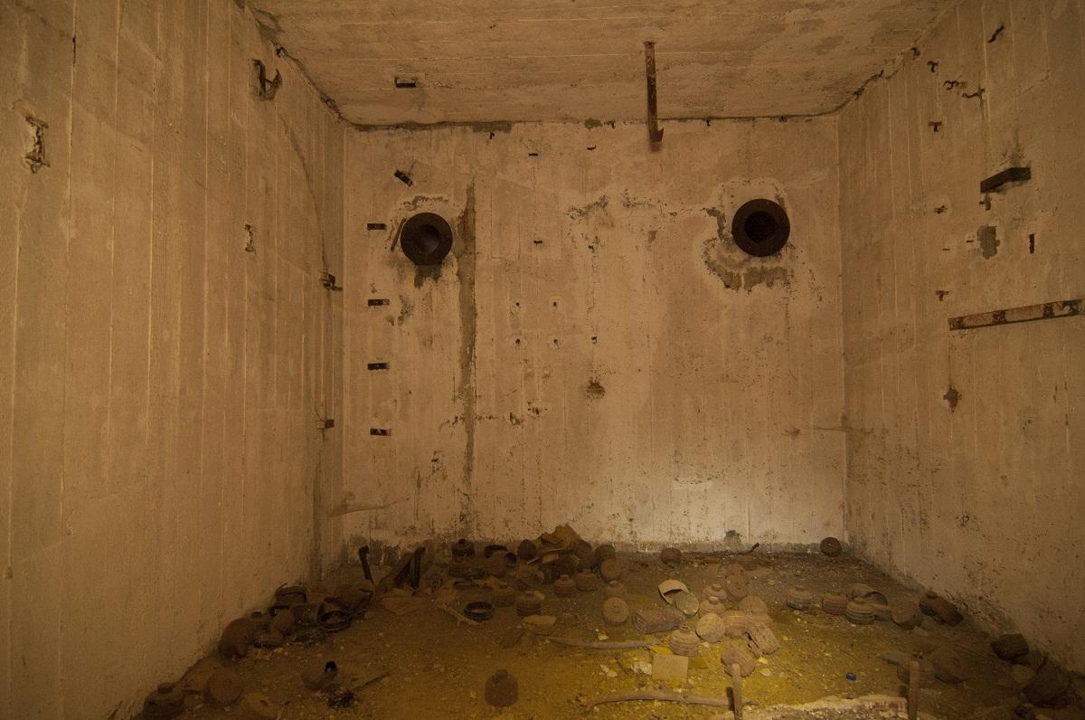 Βοηθητικός θάλαμος. Στην πάνω πλευρά του τοίχου διακρίνονται δύο σωλήνες εσωτερικής ενδοσυνεννόησης. Στο πάτωμα κείτονται ανταλλακτικά και αναλώσιμα μηχανών.