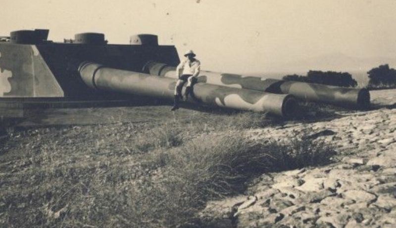 A German is sitting on one of the 305 mm guns, giving a vivid example of its size.