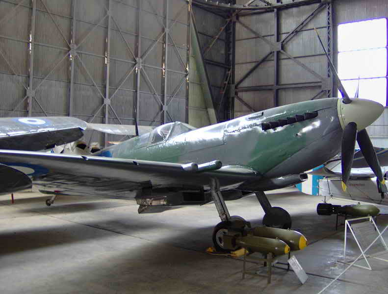 """Static display of the """"Greek"""" Spitfire inside the main hangar of the Hellenic Air Force Museum."""