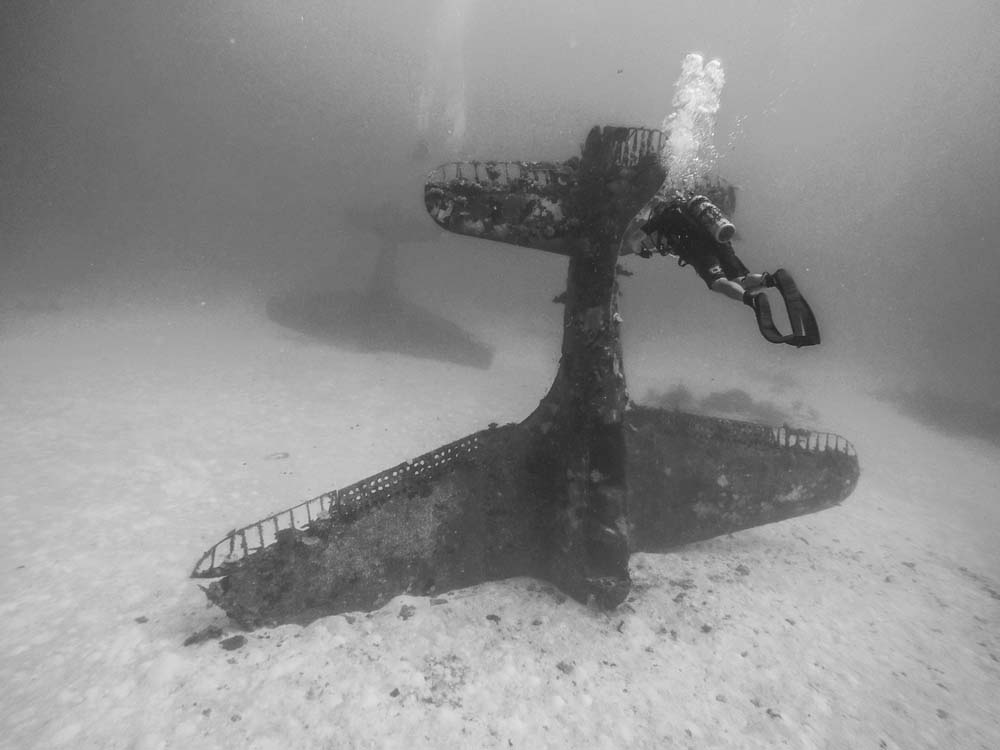 Author Dan Farnham films one of the many SBD wrecks on the lagoon bottom at Kwajalein Atoll. Behind it is another nosed-in SBD. (photo by Jessica Holland, used by permission)