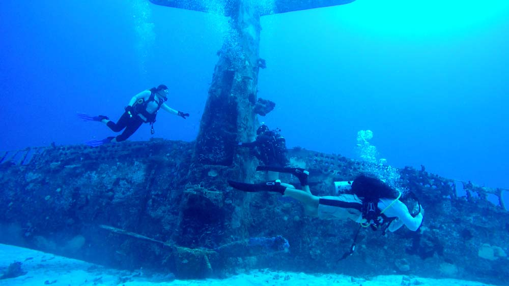Divers examine one of the many SBD wrecks at the seabed of the Kwajalein Atoll lagoon. This specific aircraft wreck sits nose down!